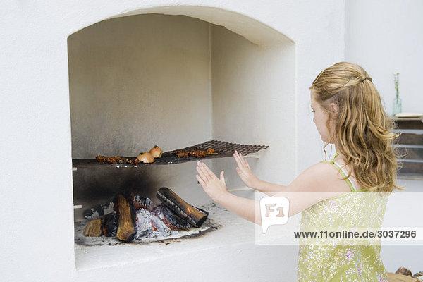 Mädchen Kochen Kebab im Kamin