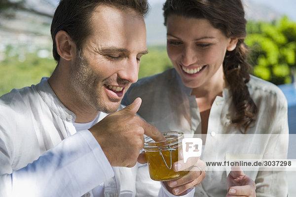 Mann hält ein Glas Marmelade mit einer Frau  die neben ihm lächelt.