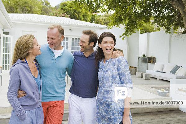 Vier Freunde stehen zusammen und lächeln