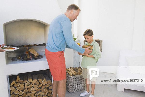 Mann kocht Kebab im Kamin  sein Sohn hält Brennholz.