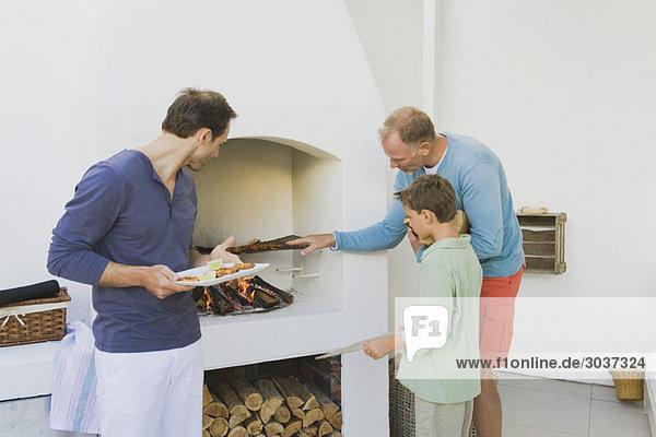 Zwei Männer mit einem Jungen  der Kebab am Kamin kocht.