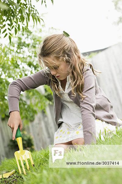 Mädchengartenarbeit mit Rechen
