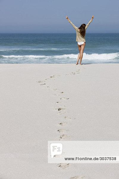 Rückansicht einer am Strand stehenden Frau mit erhobenen Armen