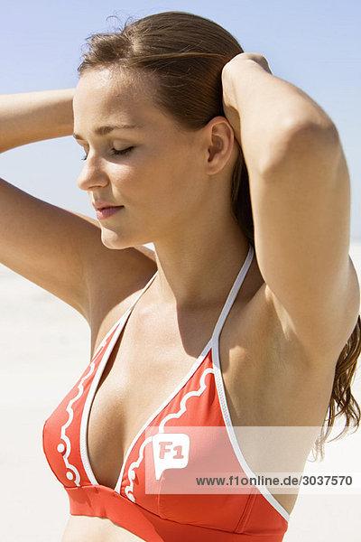 Frau am Strand stehend mit der Hand im Haar