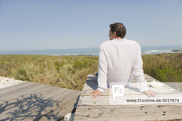 Rückansicht eines Mannes  der auf einer Strandpromenade sitzt.