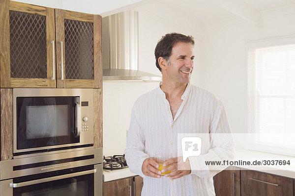 Mann hält ein Glas Saft und lächelt