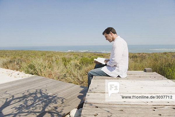 Mann sitzt auf einer Promenade und liest ein Buch.