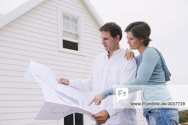 Ein Paar sieht sich einen Bauplan eines Hauses an.