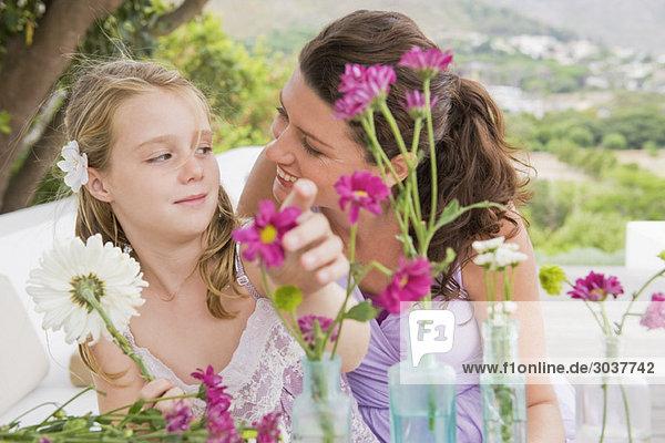 Frau mit ihrer Tochter  die Blumen in einer Vase arrangiert.
