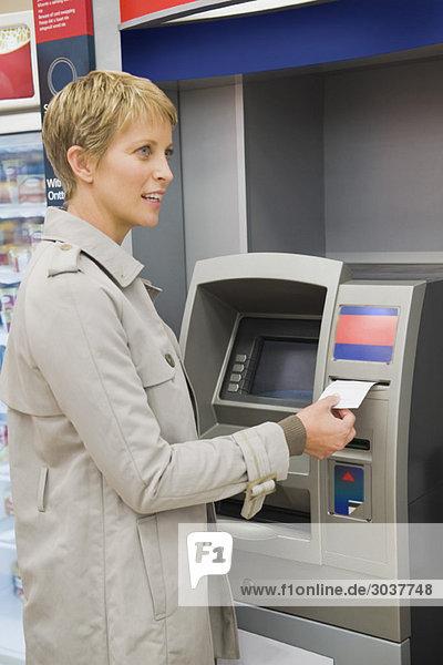 Frau  die einen Transaktionsschein von einem Geldautomaten empfängt