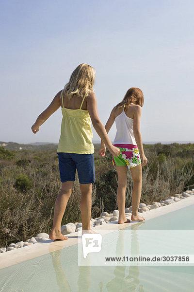 Rückansicht von zwei am Pool spielenden Mädchen