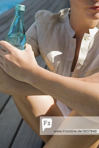 Frau sitzt auf einer Promenade und hält eine Wasserflasche.