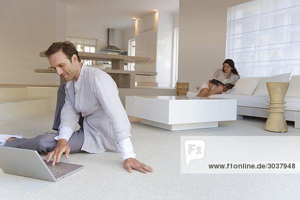 Mann  der an einem Laptop arbeitet  mit einer Frau  die im Hintergrund ein Buch liest.