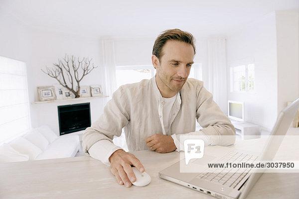 Mann arbeitet an einem Laptop und lächelt