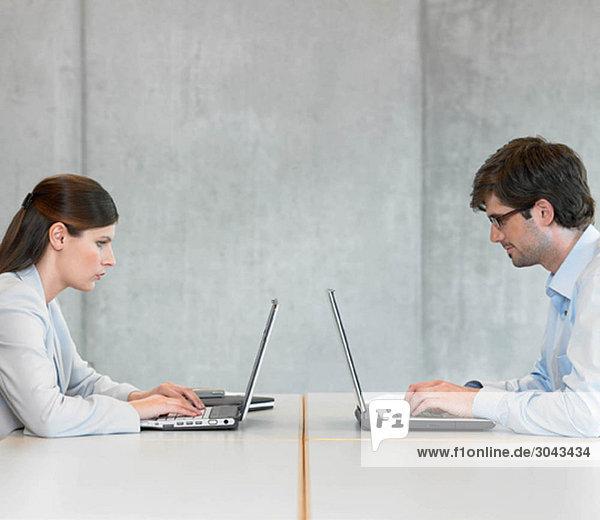 Zwei Geschäftsleute mit Laptops