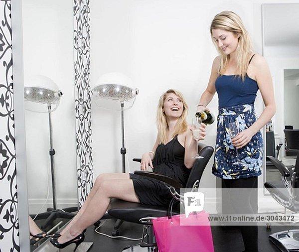 Zwei Frauen beim Friseur mit Champagner
