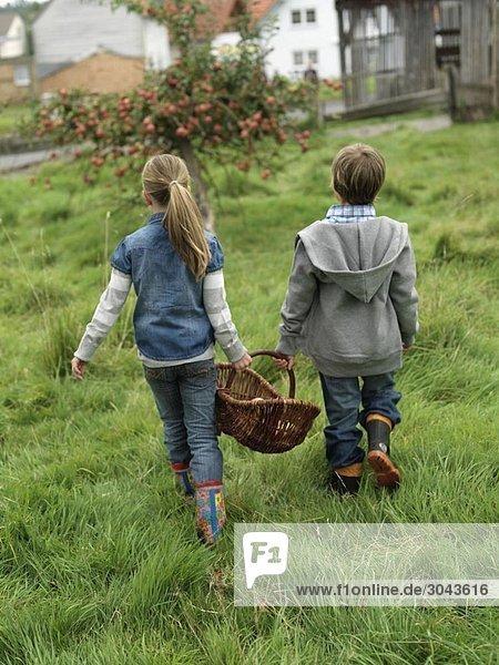 Mädchen und Junge mit Apfelkorb
