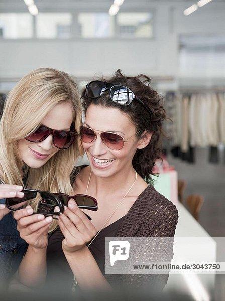women shopping comparing sunglasses