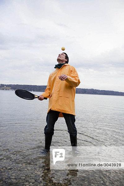 Mann im Regenmantel mit Schläger und Ball