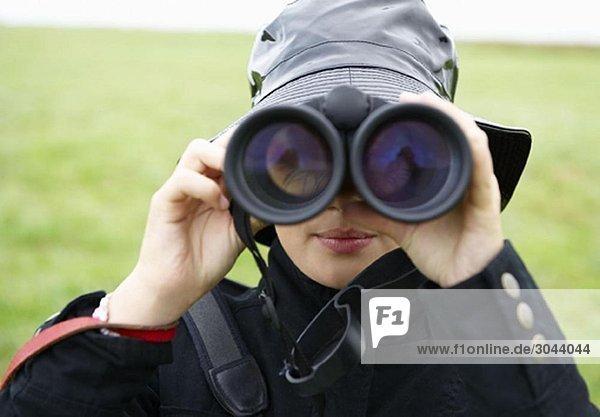 Mädchen beim Durchsehen eines Fernglases