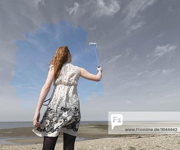Junge Frau malt grau himmelblau