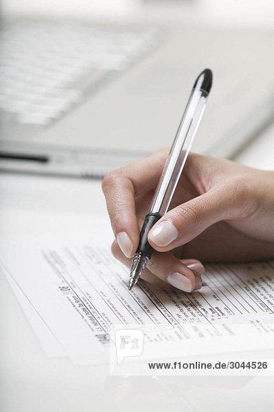 Frau beim Ausfüllen eines Steuerformulars
