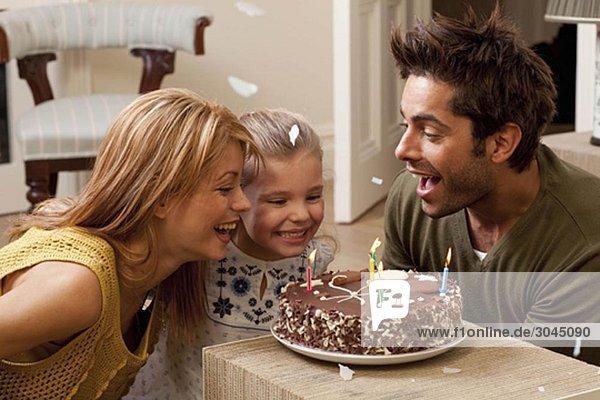Eltern und Kind beim Ausblasen von Kerzen
