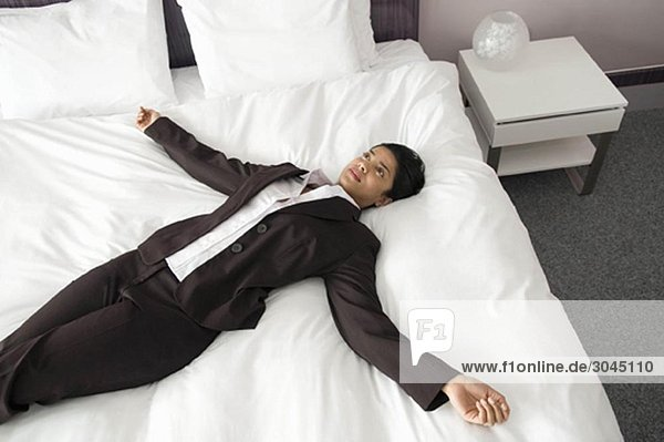 Frau auf einem Bett mit ausgestreckten Armen
