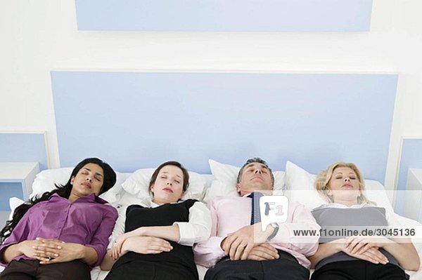 Vier Geschäftsleute im Bett