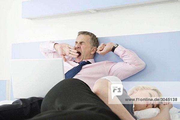 Ein müdes Geschäftspaar im Bett