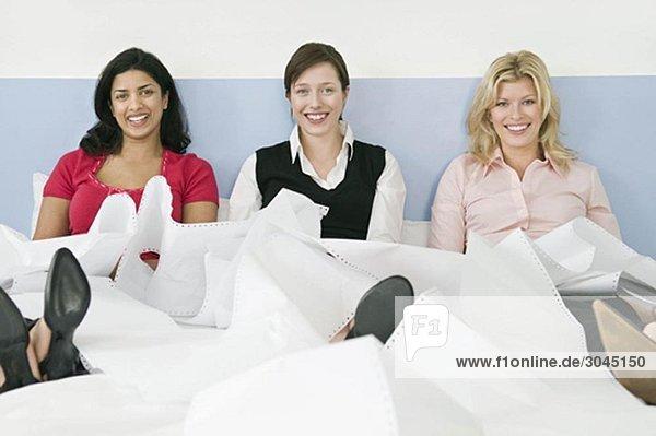 Drei Kolleginnen im Bett sitzend