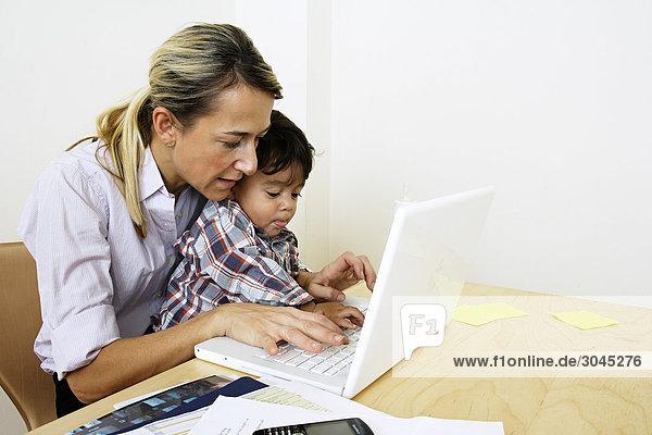 Frau mit Laptop-Computer mit kleinen Sohn am Tisch sitzend von zu Hause arbeiten