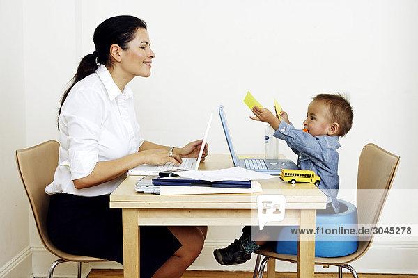 Frau Arbeit von zu Hause sitzen am Tisch mit kleinen Sohn