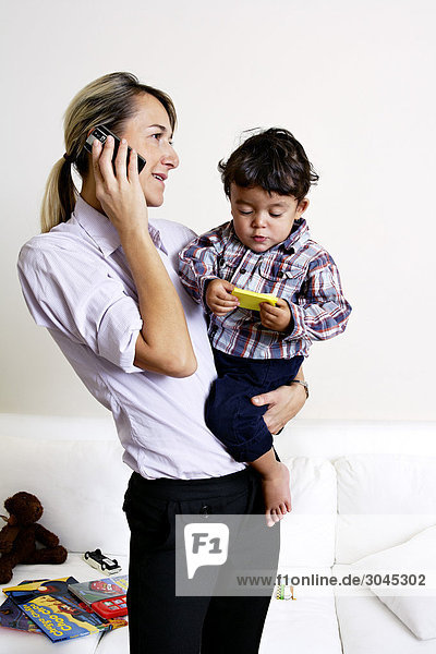 Mutter hält kleiner Sohn und sprechen auf Handy