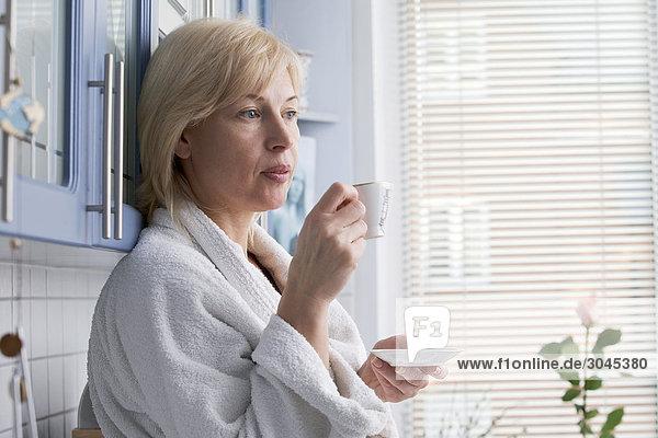 portrait of woman in bathobe drinking coffee