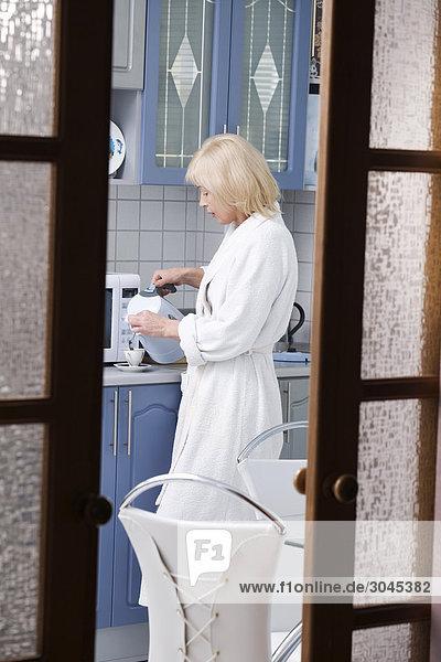zeigen Sie in Küche mit Frau im Bademantel Gießen Kaffee in Cup an