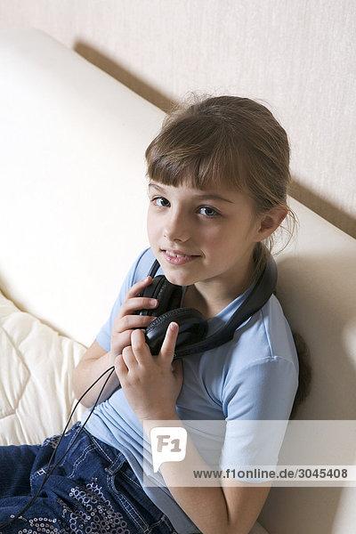 Porträt der jungen Mädchen sitzen auf Sofa mit Kopfhörern