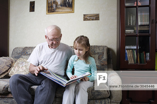 älterer Mann lesen Buch mit Enkelin