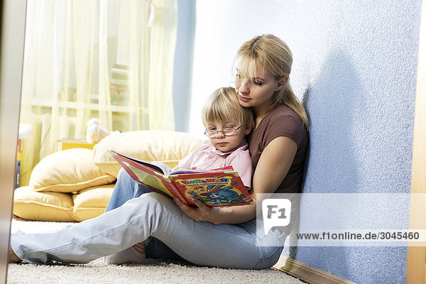 young mother reading from book to her son