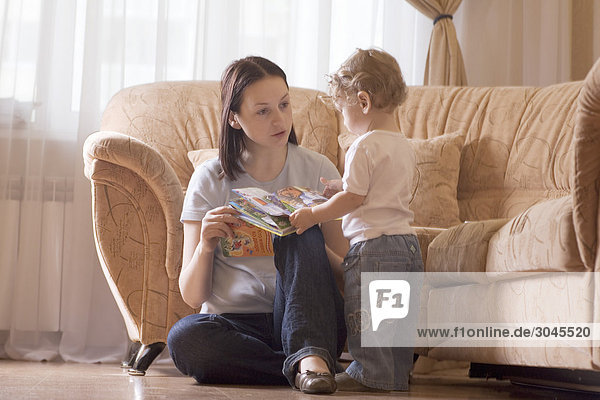 mother sitting on floor in living room reading book to her young son