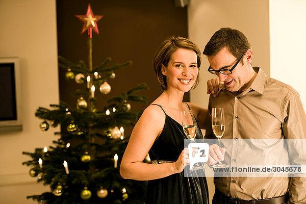 paar erhöhen ihre Gläser am Weihnachtsabend