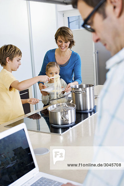 father working with laptop computer while mother and children are preparing meal