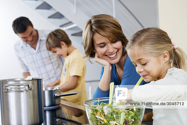 parents cooking with their children in kitchen