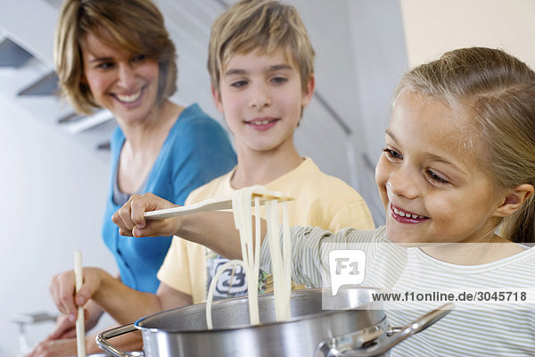mother and brother watching young girl cooking spaghetti