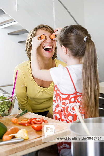 mother and daughter having fun with carrot slices in kitchen