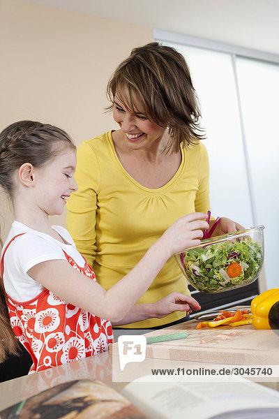 junge Mädchen und Mutter machen Salat