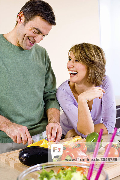 couple cooking together in kitchen man cutting vegetables