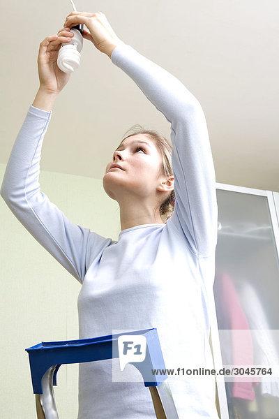 junge Frau Befestigung niedrige Energie-Glühlampe