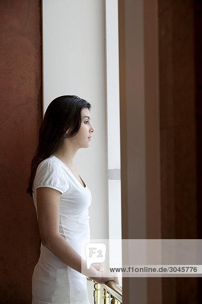 Porträt von Teenagerin Blick aus Fenster