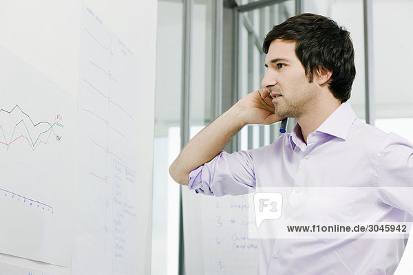 portrait of young businessman in front of whiteboard